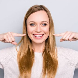 Woman pointing at her smile
