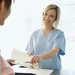 Smiling team member giving patient paperwork