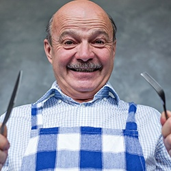 person smiling and holding a knife and fork