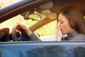 woman struggling to stay awake in car